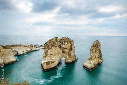 Fototapeta premium Rouche skały w Bejrucie w Libanie w pobliżu morza i podczas zachodu słońca. Pochmurny dzień w Bejrucie w Libanie na Pigeon Rocks na Morzu Śródziemnym.