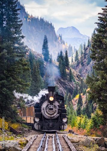 Fototapeta Steam Train Crossing a Trestle Bridge in the Mountains