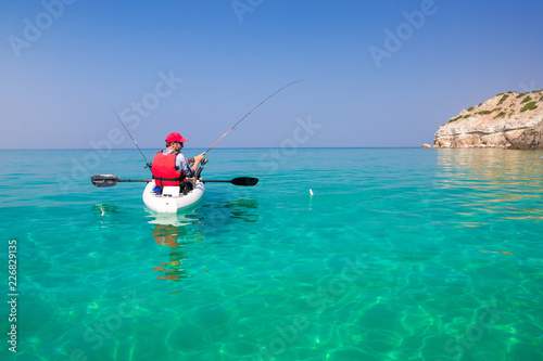 Fotografiet Man fishing on a kayak in the sea with clear turquoise water