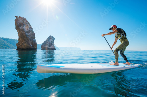 Stand up paddle boarding. Young man floating on a SUP board. The adventure of the sea with blue water on a surfing.
