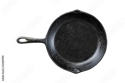 Old black cast iron pan isolated over a white background with clipping path included. Image of skillet shot from overhead.