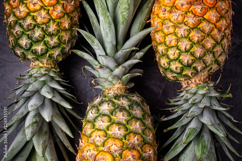 Close up of three ripe fresh pineapples on dark background , top view