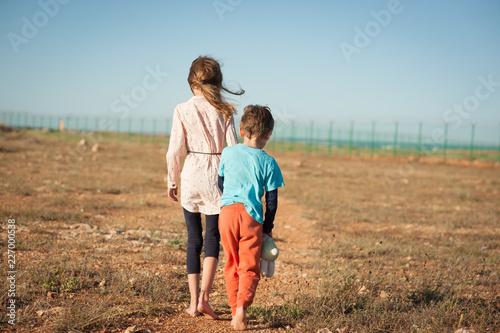 little boy and girl refugees walking alone in desert towards border with fence Fototapeta