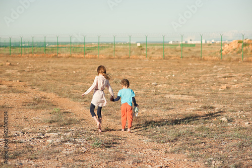 Obraz na płótnie poor small girl and boy refugees walk in desert towards fencing with barbed wire