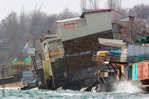 Photo Coastal erosion - houses built on weak clay soil slide down to the sea and colla