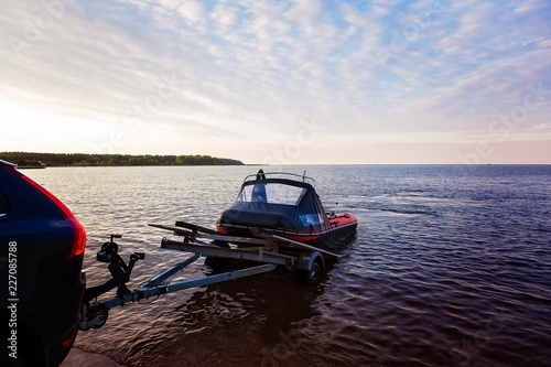 Loading a rubber boat on a trailer on the lake at sunset