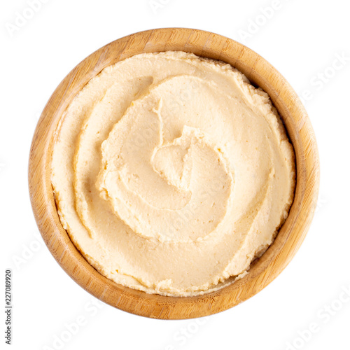 Classic chickpea hummus in wooden bowl isolated on white.