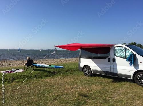 Entspannte Pauseunter dem roten Sonnenschutz  mit dem Camper am Meer