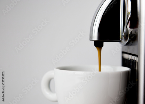 Slika na platnu Coffee Machine and Empty Cup Ready for Pouring Beverage on White Wall Background