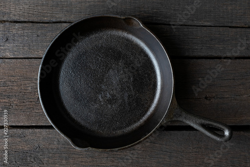 Empty black cast iron pan isolated on dark painted wood from above.