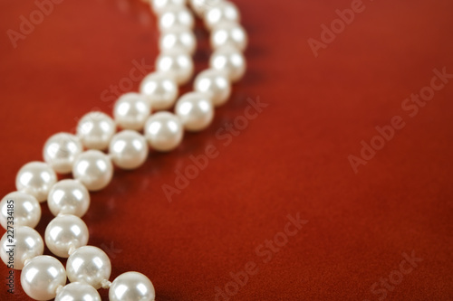 White pearl necklace on red leather background. Fototapeta