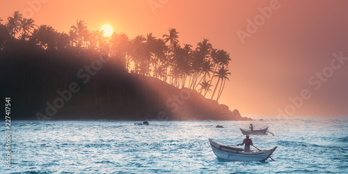 Canvas Print Tropical beach on sunset with fishermen and sea