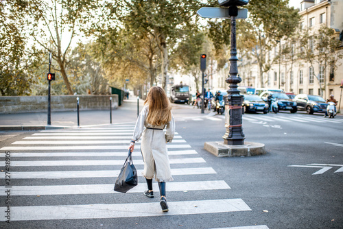 Cityscape view with woman crossing the street during the morning light in Paris, Fototapeta