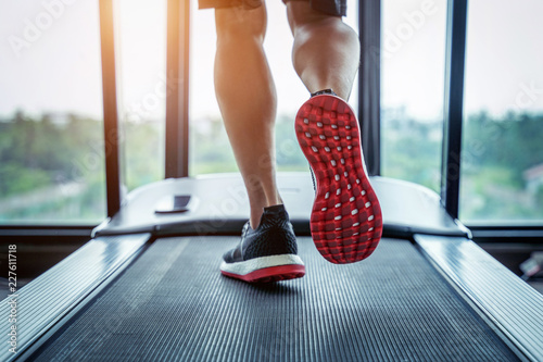 Fotografia Male feet in sneakers running on the treadmill at the gym
