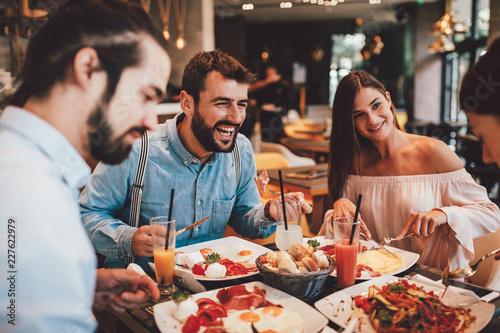 Group of Happy friends having breakfast in the restaurant