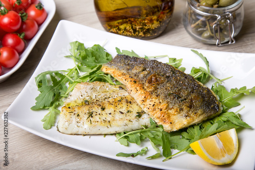 Fotografia Grilled seabass fillet with arugula, lemon, tomatoes and capers
