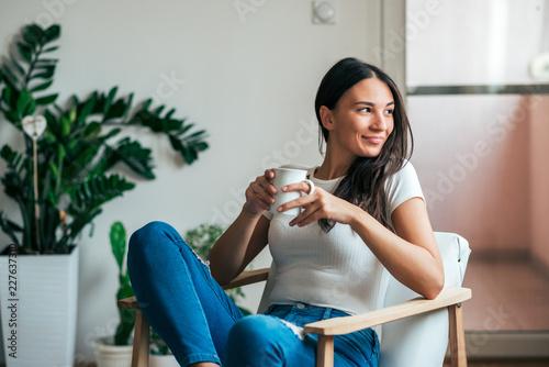 Carta da parati Beautiful young woman drinking tea at home. Looking away.