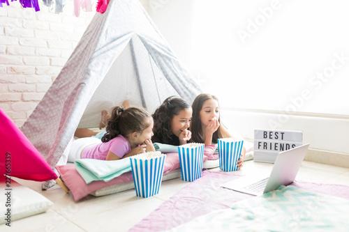 Fotografia Female Friends Enjoying Snacks While Watching Laptop In Tent