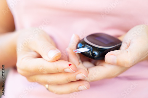 Measuring blood sugar level with blood glucose metr, world diabetes day concept