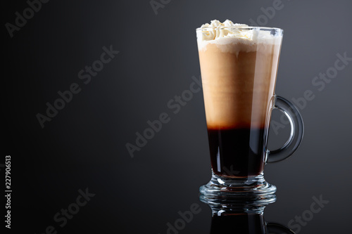 Coffee drink or cocktail with cream on a black background.