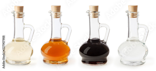 White, apple cider and balsamic vinegar in glass bottles isolated on white background