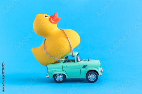Photographie Rubber duck and small car toys abstract isolated on blue.