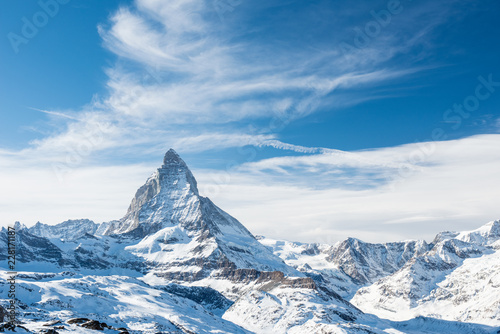 Canvas Print Scenic view on snowy Matterhorn peak in sunny day with blue sky and dramatic clouds in background, Switzerland