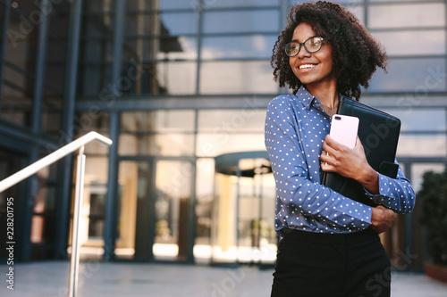 Obraz na plátně Happy business woman standing outside a office building