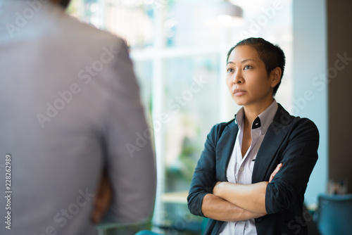 Stampa su Tela Tense Asian businesswoman looking at male partner with crossed arms
