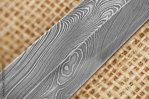 Tela Traditional handmade Finnish knife with the abstract wave pattern of damascus steel over an old sack background