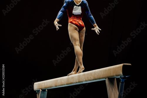 performance female gymnast on balance beam on black background