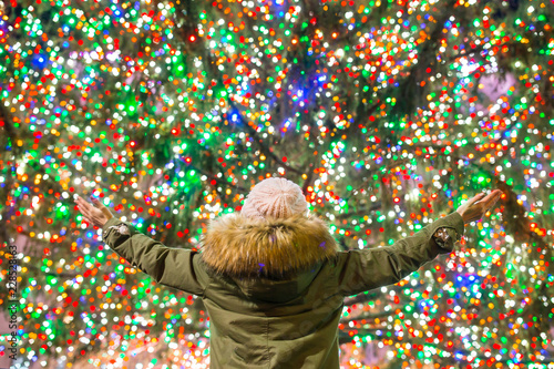 Photo Happy girl on the background of the Rockefeller Christmas tree in New York