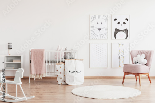 Tapete Stylish scandinavian nursery with white furniture and pink accents, cute poster on the white empty wall with copy space