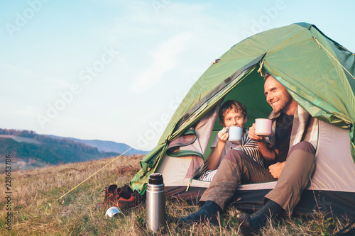 Family lisure concept image. Father and son drink a tea sitting in touristic tent