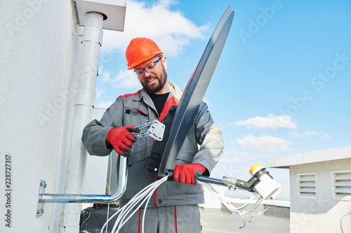 Service worker installing and fitting satellite antenna dish for cable TV Fototapete