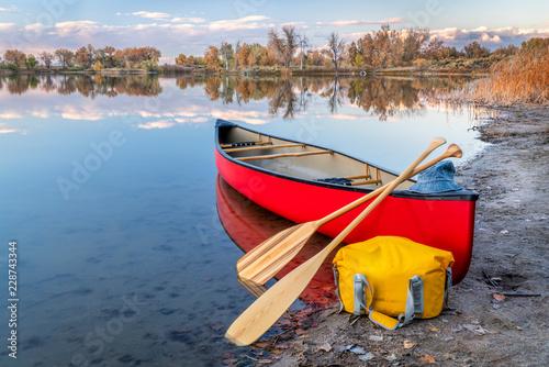 Cuadros en Lienzo red canoe on a lake shore