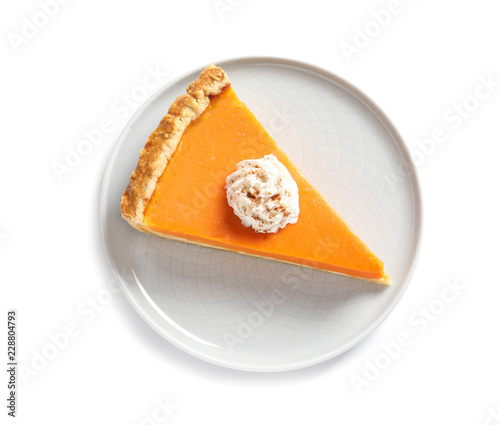 Plate with piece of fresh delicious homemade pumpkin pie on white background, top view