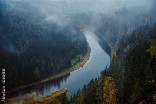 Autumn landscape: fog over the river in the autumn forest, top view. Wilderness.