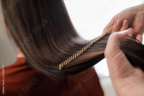 Close up of hairdresser making hair styling for woman while combing by hairbrush Fototapeta