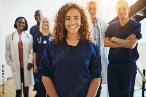 Smiling female doctor standing with medical colleagues in a hosp