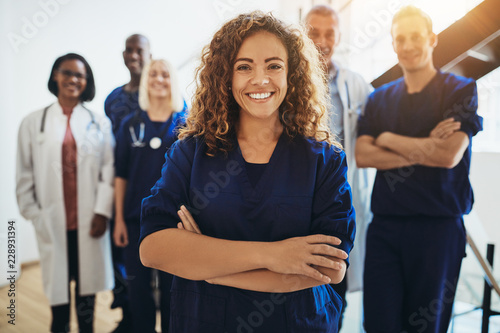 Smiling female doctor standing with medical staff in a hospital