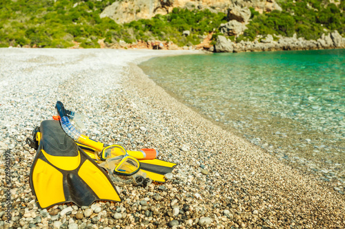 Flippers and snorkeling tube on sea shore
