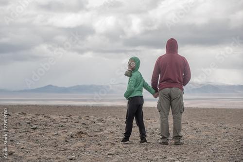 Carta da parati father and son in a gas mask in the desert steppe