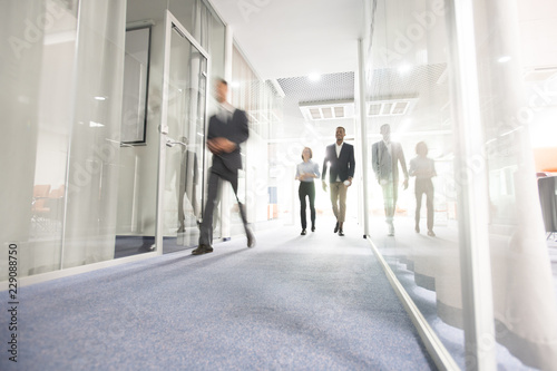 Photo Blurred motion of modern business people crossing illuminated office corridor wh
