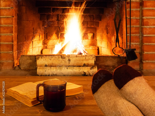 Photo Cup of tea, book, women's feet in warm socks on a wooden table opposite a burnin