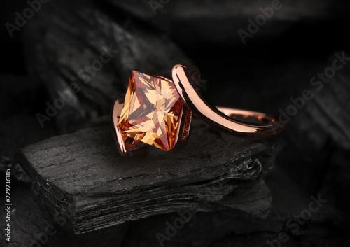 Vászonkép jewelry ring with big topaz gem on black coal background