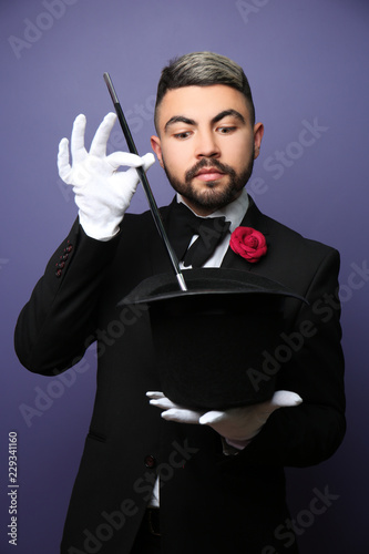 Canvas Print Male magician showing tricks with hat on color background