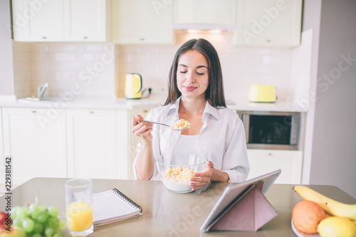 Beautiful young woman sits at table and eats milk with corn flakes фототапет