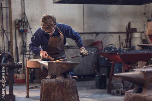 Fotografia Young blacksmith working with red hot metal