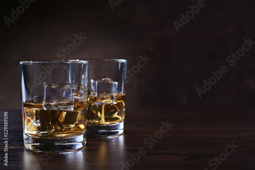 Glasses with whiskey and ice cubes